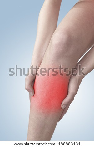 Acute pain in a knee. Woman holding hand to spot of knee-aches. - stock photo