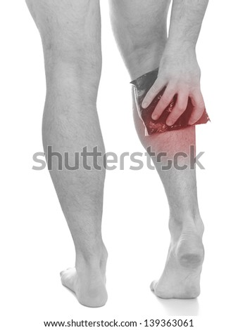 Acute pain in a man calf. Male holding ice pack  on calf-aches. Medical concept photo. Isolation on a white background. - stock photo
