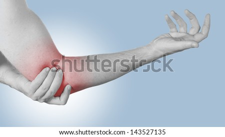 Acute pain in a man elbow. Male holding hand to spot of elbow pain. - stock photo