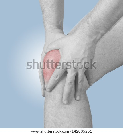 Acute pain in a man  knee. Male holding hand to spot of knee-aches - stock photo