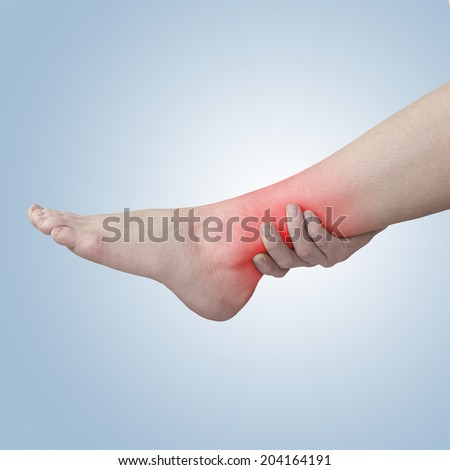 Acute pain in a woman ankle. Woman holding hand to spot of ankle-aches.