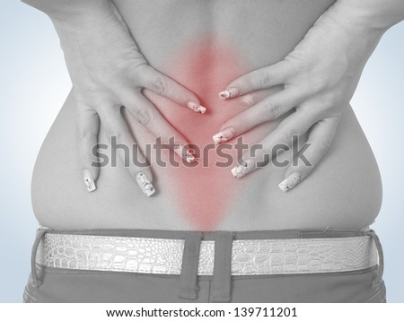 Acute pain in a woman back. Female from behind holding hand to spot of back pain. Concept photo with read spot indicating location of the pain. Isolation on a white background.  - stock photo