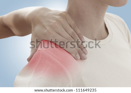 Acute pain in a woman shoulder. Female holding hand to spot of shoulder-aches. Concept photo with Color Enhanced skin with read spot indicating location of the pain. - stock photo