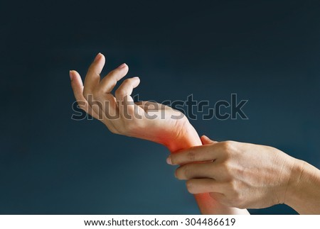 Acute pain in a woman wrist, colored in red on dark blue background, Health issues problems  - stock photo