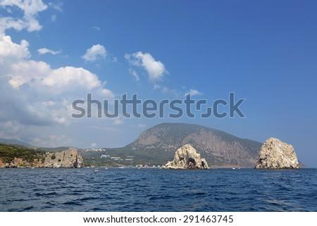 Adalary Rocks (White stones) - small rocky Islands in the Black sea near Gurzuf on the background mountain Ayu-Dag (Medved'-gora, Bear mountain) - the landmark of the southern coast of Crimea, Russia - stock photo