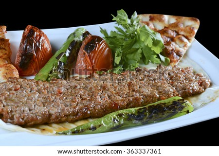 Adana kebab is a long, hand-minced meat kebab mounted on a wide iron skewer and grilled on an open mangal filled with burning charcoal.