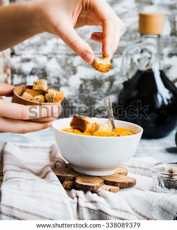 add croutons in pumpkin soup with carrots, croutons in a white dish, ,rustic,hands