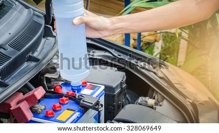 Add distilled water in battery by user,maintenance car by itsalf - stock photo