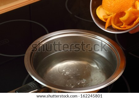 Add orange peel into saucepan with boiling syrup. Candied Orange Zest Cooking. Series. - stock photo