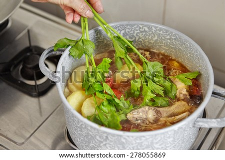Add parsley to the cooking in pan - stock photo