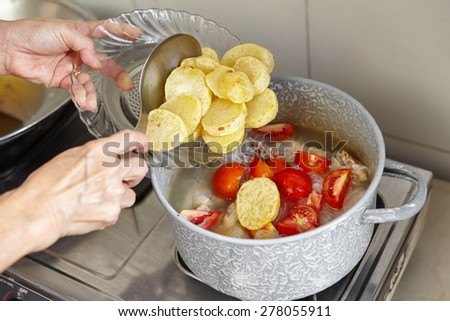 Add potato to the cooking in pan - stock photo
