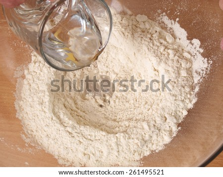 Add water into flour. Making Puff Pastry Series. - stock photo