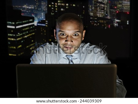 addict businessman alone at night sitting at office computer laptop watching porn, online gambling or working late in addiction concept  - stock photo