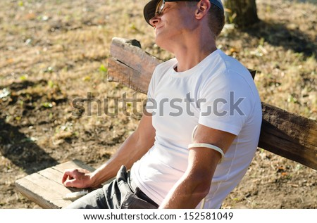 Addicted Caucasian man sitting on a bench in the park feeling side effects after injecting a drug dose intravenously - stock photo