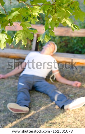 Addicted Caucasian middle-aged man lying down on the ground leaning his head on a bench feeling sick because of drug abuse - stock photo