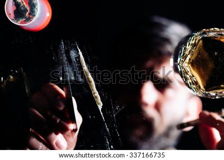 Addicted man preparing a line of cocaine.  - stock photo