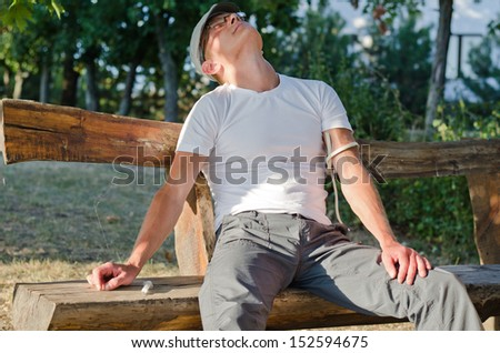 Addicted man sitting on a bench in the park feeling side effects after injecting a drug dose intravenously - stock photo