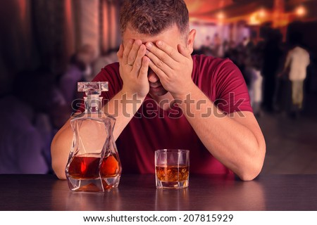 Addicted to alcohol man drinking alone at the bar - stock photo