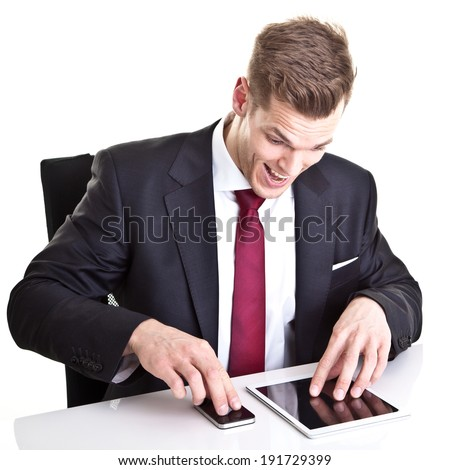 Addicted to his electronic devices - young businessman using tablet and smart phone at the same time and making a crazy facial expression. Isolated on white - stock photo
