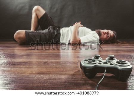 Addiction and dependency concept. Young man with pad joystick playing games. Male addicted to console videogames. - stock photo