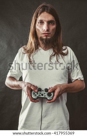 Addiction and dependency concept. Young man with pad joystick playing games. Male addicted to console playstation videogames. - stock photo