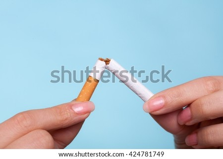 Addiction. Closeup of female hands breaking the cigarette on blue. Quit smoking. Studio shot. - stock photo