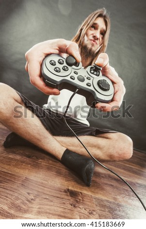 Addiction effects concept. Young unhappy depressed man with pad joystick playing games. Male addicted to console playstation videogames. - stock photo