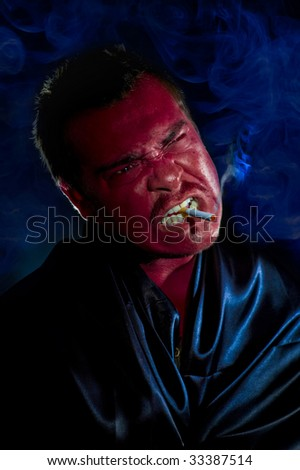 addiction: the evil is smoking a cigarette in the dark - stock photo