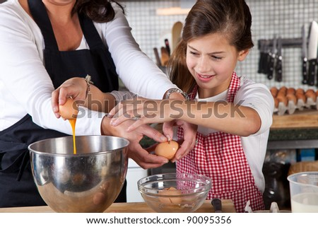 Adding an egg into the mixing bowl - stock photo