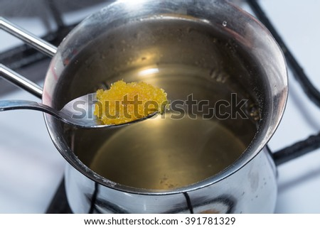 Adding brown sugar to melted gelatin in metal pot. Macro. Photo can be used as a whole background. - stock photo