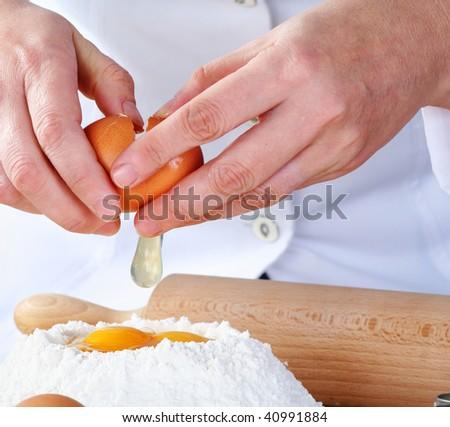 adding egg to the flour - stock photo