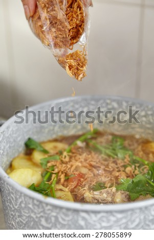 Adding fried shallot to the cooking in pan - stock photo