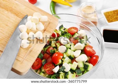Adding mozzarella cheese to salad, at kitchen - stock photo