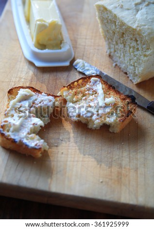Adding softened butter to toast from loaf of homemade bread - stock photo
