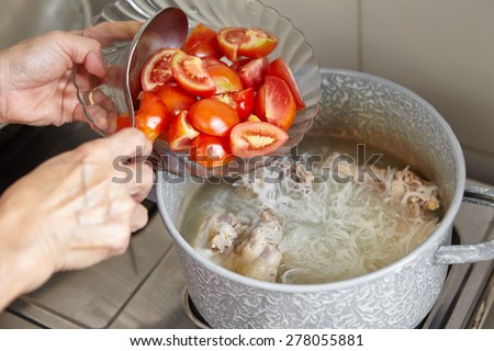 Adding tomato to the cooking in a pan - stock photo
