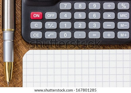 Adding up figures concept with calculator, pen and notepad on the table - stock photo