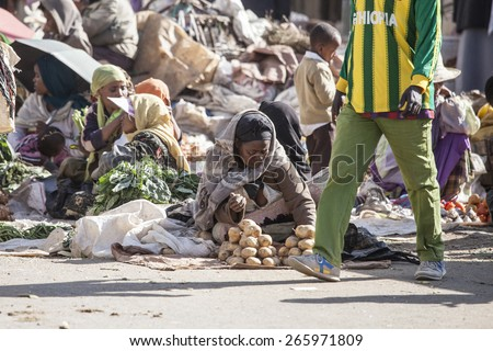 ADDIS ABABA, ETHIOPIA-October 31, 2014 Unidentified women and children sell vegetables at an outdoor market in Addis Ababa, Ethiopia - stock photo
