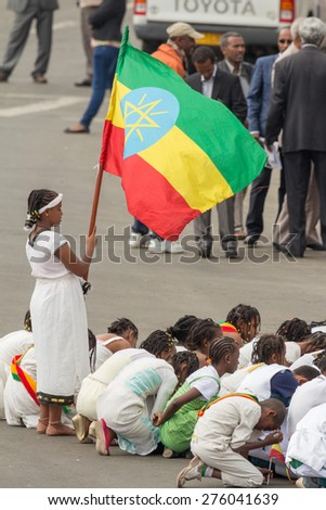 Addis Ababa - May 5: A young girl dressed in colourful traditional outfit holds the Ethiopian flag at the 74th anniversary of Patriots' Victory day on May 5, 2015 in Addis Ababa, Ethiopia. - stock photo