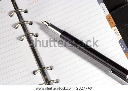 Address book with tabs, fountain pen on top. - stock photo