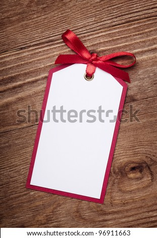 address card with bow on old wooden background. - stock photo