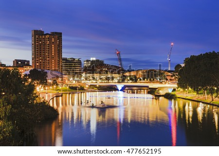 Adelaide city CBD at sunrise view across Torrens river from park footbridge. Illuminated modern city buildings reflecting in still river waters.