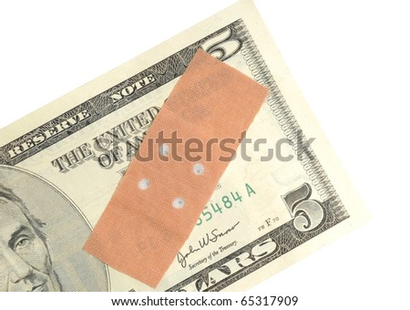 Adhesive bandage on a banknote as symbol for the weakness of a currency