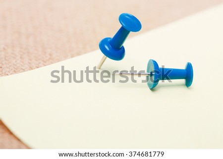 Adhesive note and blue pushpins. Close-up view