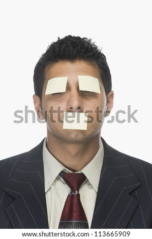 Adhesive notes on the eyes and mouth of a businessman - stock photo
