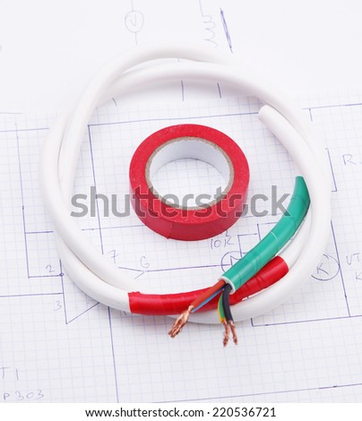 Adhesive plastic tape and electric cable on the background on the electric scheme - stock photo