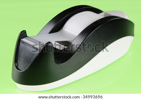 adhesive tape dispenser on green background