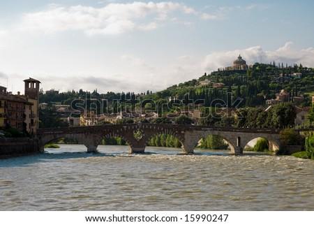 Adige river and stone bridge, with Nossa Signora de Lourdes Sanctuary in the background. - stock photo