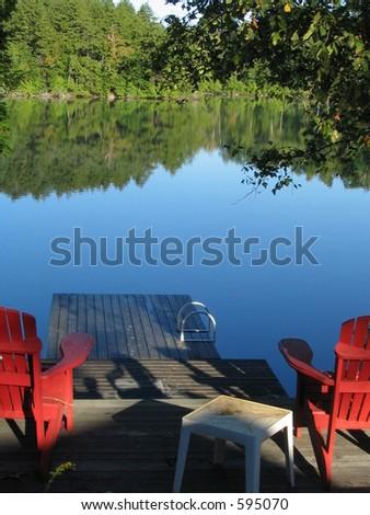 adirondack chairs facing the lake - stock photo