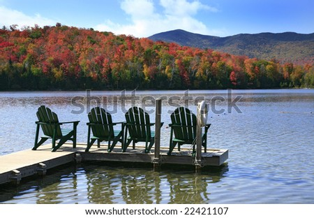 Adirondack chairs on a swim dock, on a peaceful lake in the Adirondack State Park in New York State. - stock photo