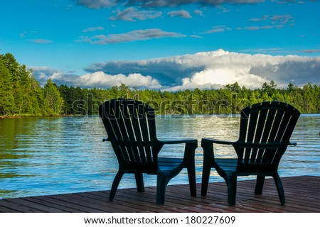 Adirondack chairs on pier viewing a peaceful lake - stock photo